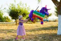 Young girl at an outdoor party hitting a pinata